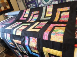 Quilt top laying laying across longarm