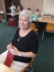 Marie handsews a purse