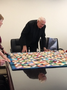 Fr looking at quilt at presentation
